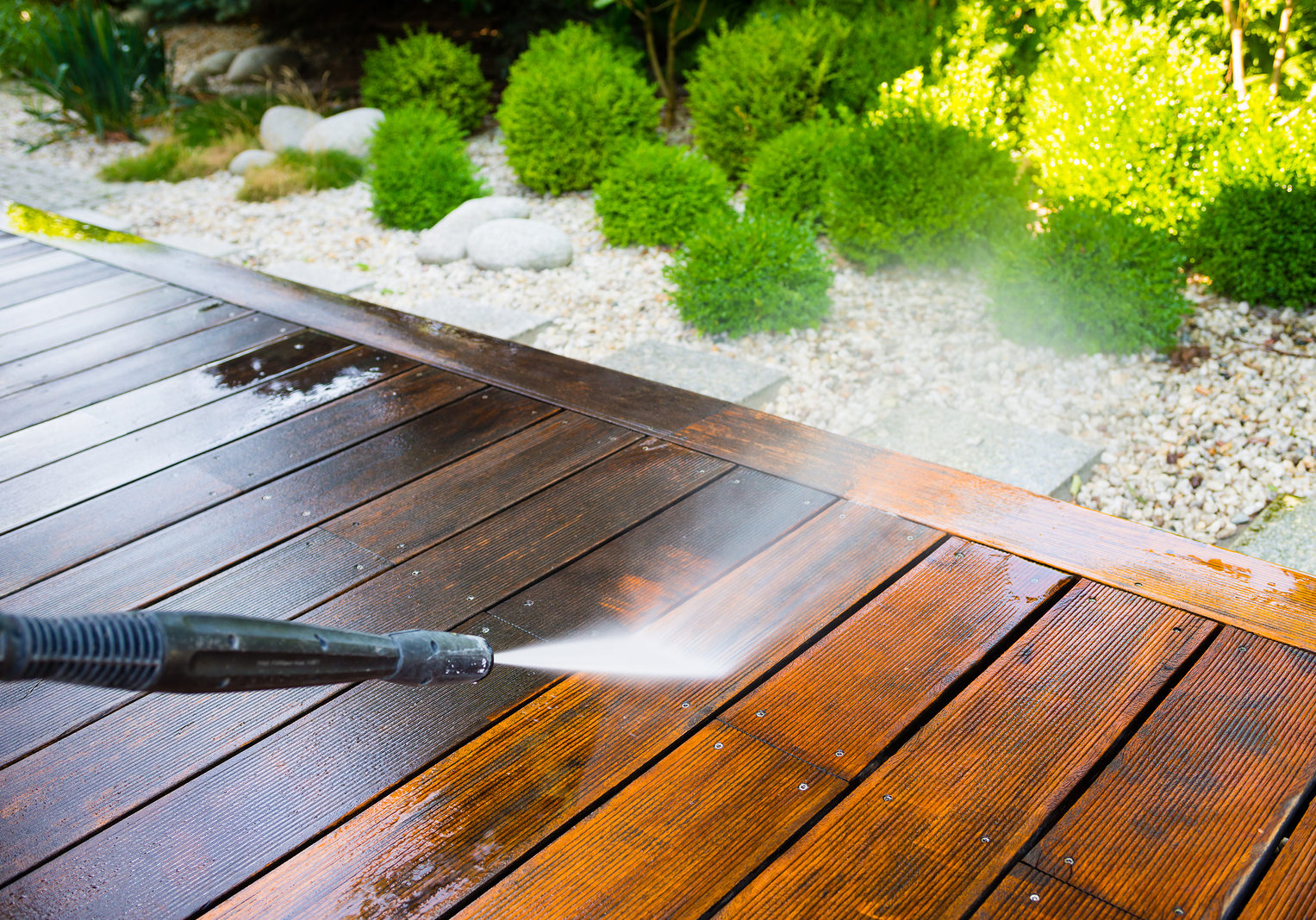 Cleaning Terrace With A Washer High Water Pressure Cleaner On Wooden Surface